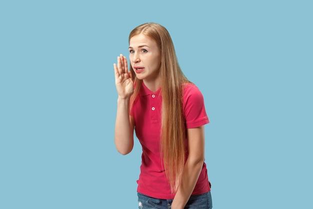 Die junge frau flüstert ein geheimnis hinter ihrer hand über blau