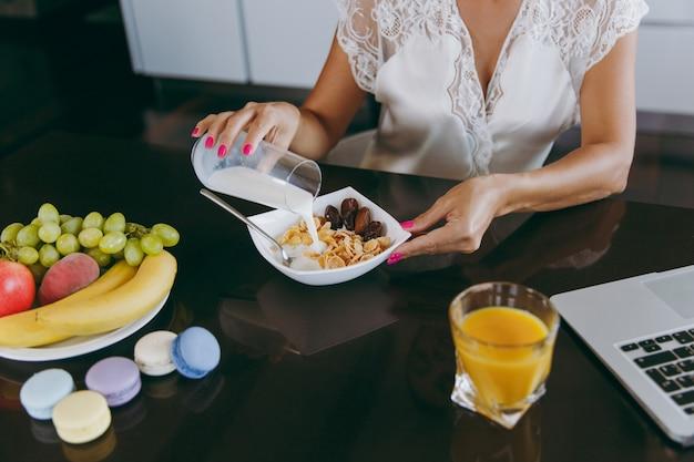 Die junge frau gießt milch in eine schüssel mit müsli zum frühstück mit einem laptop auf dem tisch
