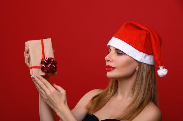 Die junge frau in einer weihnachtsmütze erwägt ein weihnachtsgeschenk