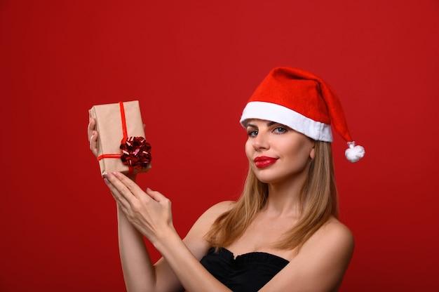 Die junge frau in einer weihnachtsmütze hält ein weihnachtsgeschenk.