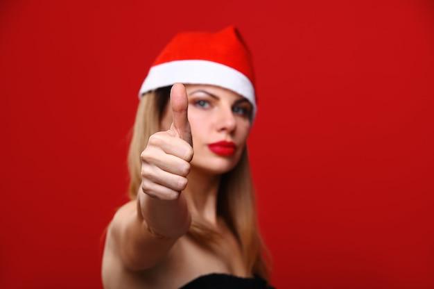 Die junge frau in einer weihnachtsmütze lächelt und zeigt ihren daumen. das konzept von weihnachten.