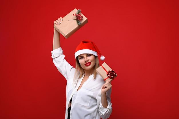 Die junge frau in einer weihnachtsmütze mit weihnachtsgeschenken in der hand.