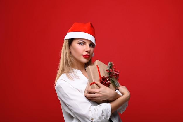 Die junge frau in einer weihnachtsmütze umarmt geschenke. das konzept von weihnachten.