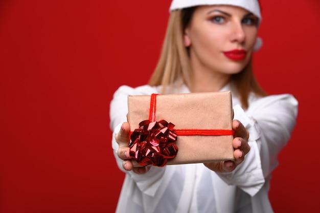 Die junge frau in einer weihnachtsmütze zeigt der kamera ein weihnachtsgeschenk. konzentrieren sie sich auf das geschenk.