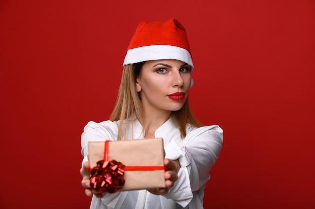 Die junge frau in einer weihnachtsmütze zeigt der kamera ein weihnachtsgeschenk. konzentrieren sie sich auf das modell.