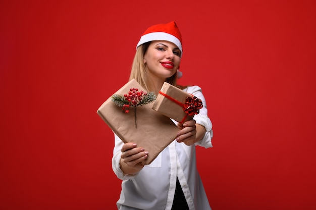 Die junge frau in einer weihnachtsmütze zeigt der kamera geschenke.