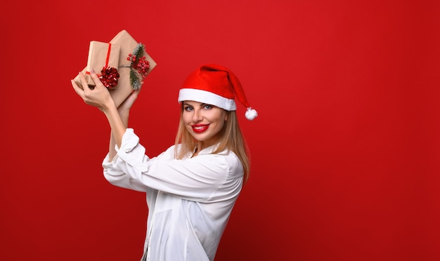Die junge frau in einer weihnachtsmütze zeigt weihnachtsgeschenke steigend und hoch.