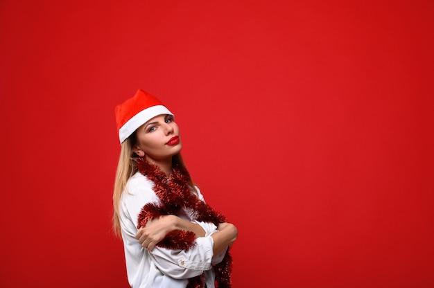 Die junge frau in santas hut mit einer weihnachtsbaumgirlande um den hals. das konzept von weihnachten.