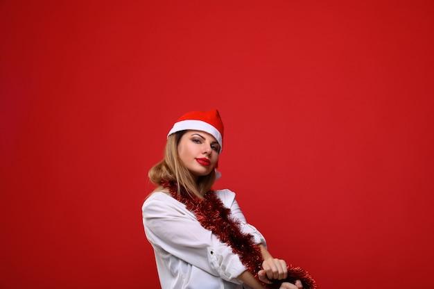 Die junge frau in santas hut mit einer weihnachtsbaumgirlande um den hals.