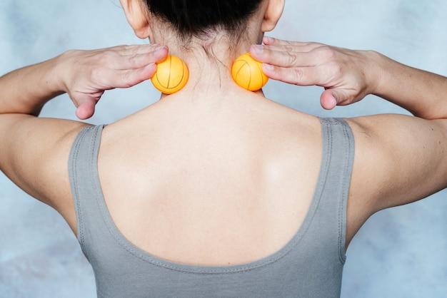 Die junge frau massiert ihren hals mit einem triggerpunkt-tennisball, der zur linderung von muskelschmerzen verwendet wird