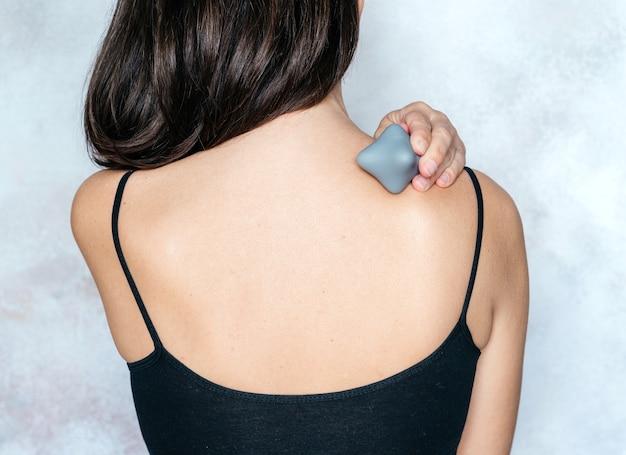 Die junge frau massiert ihren rücken mit einem triggerpunktball, der zur direkten linderung von muskelschmerzen verwendet wird