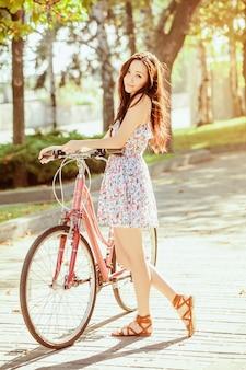 Die junge frau mit dem fahrrad im park