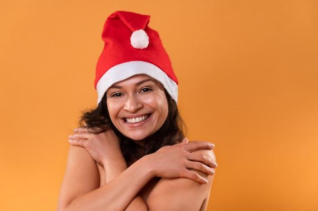 Die junge frau mit weihnachtsmannmütze umarmt sich und lächelt.