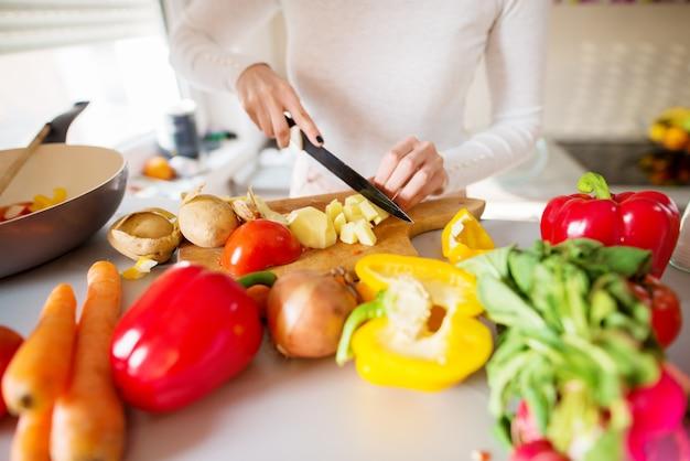 Die junge frau schneidet tomaten und kartoffeln und bereitet das frühstück vor, während sie vor einer küchentheke steht, die mit frischem gemüse gefüllt ist.