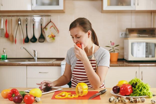 Die junge frau sitzt am tisch und sucht in der küche auf dem tablett nach einem rezept. gemüsesalat. diätkonzept. gesunder lebensstil. kochen zu hause. essen zubereiten.