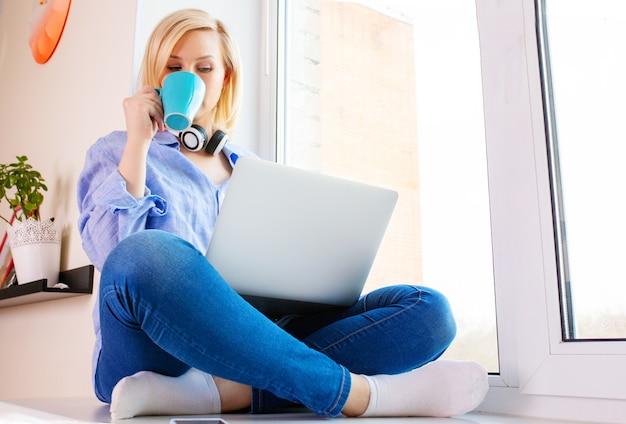 Die junge frau sitzt auf der fensterbank und arbeitet am laptop