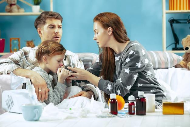 Die junge frau und der mann mit der kranken tochter zu hause. behandlung zu hause. mit einer krankheit kämpfen. medizinische gesundheitsversorgung. familienhaftigkeit. der winter, influenza, gesundheit, schmerz, elternschaft, beziehungskonzept