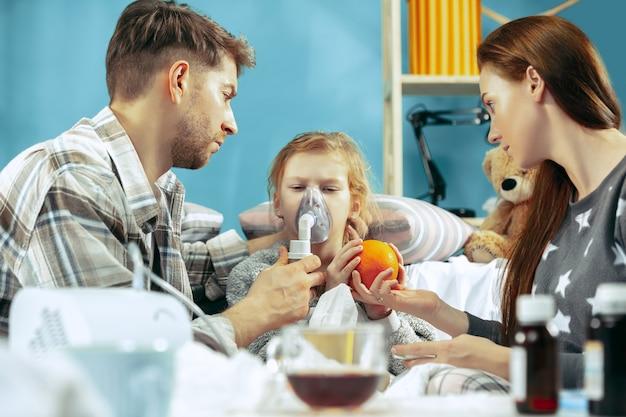 Die junge frau und der mann mit der kranken tochter zu hause. behandlung zu hause. mit einer krankheit kämpfen. medizinische gesundheitsversorgung