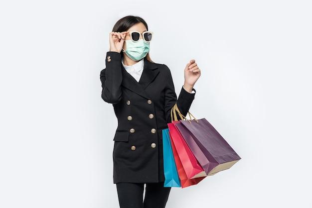Die junge frau war dunkel gekleidet, trug eine maske, eine brille und taschen, um einkaufen zu gehen