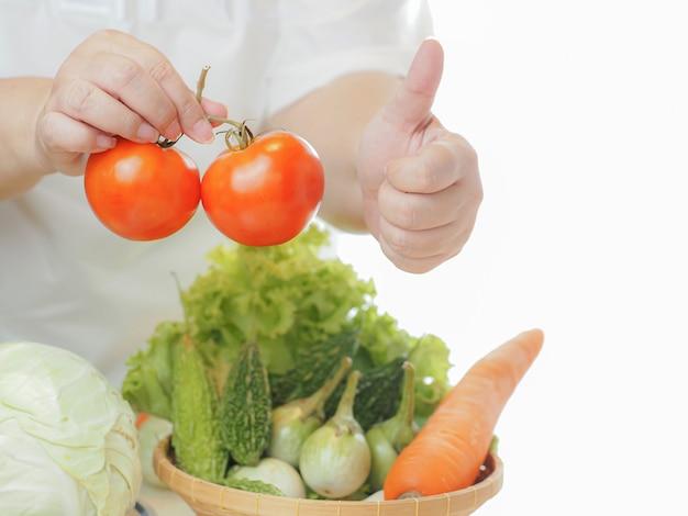 Die junge frau zeigt mit dem daumen nach oben, dass frisches gemüse nützlich ist