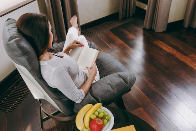 Die junge frau zu hause sitzt auf einem modernen stuhl vor dem fenster, entspannt sich in ihrem wohnzimmer und liest ein buch
