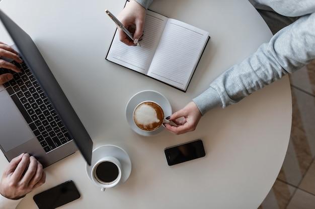 Die junge freiberuflerin sitzt an einem tisch mit einem geschäftsmann in einem café, trinkt kaffee und macht einträge in einem notizbuch