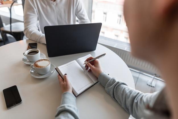 Die junge freiberuflerin sitzt mit einem notizblock in einem café und macht sich notizen, während sie einem geschäftspartner aufmerksam zuhört