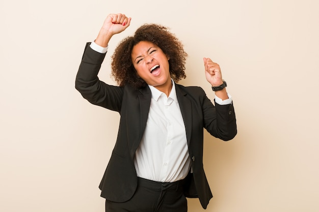 Die junge geschäftsafroamerikanerfrau, die einen speziellen tag feiert, springt und hebt arme mit energie an.