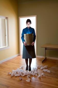 Die junge geschäftsfrau, die im büro steht und einen belichteten abfalleimer hält, zerknitterte papiere auf dem boden