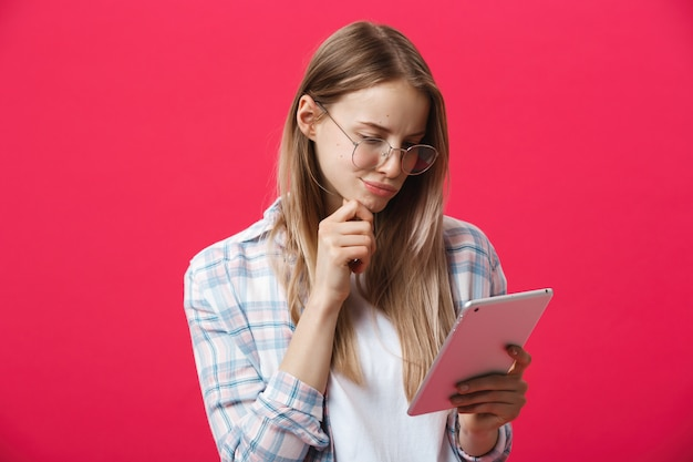Die junge geschäftsfrau, die tablette hält und denkt an rosa backgrouond