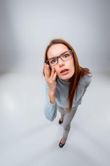 Die junge geschäftsfrau in gläsern auf einem grauen raum. draufsicht