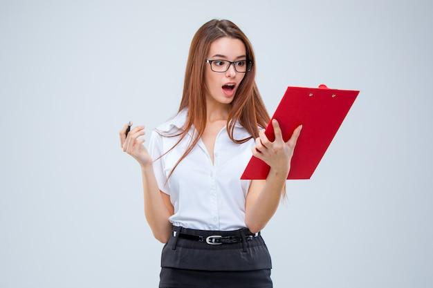 Die junge geschäftsfrau mit stift und tablette für anmerkungen über graue wand