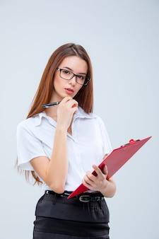 Die junge geschäftsfrau mit stift und tablette für notizen auf grau