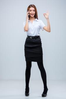 Die junge geschäftsfrau mit telefon auf einem grau