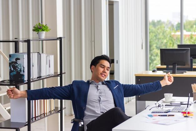 Die junge geschäftsmannarbeitskraft, die pause beim entspannenden sitzen der arbeit im ergonomischen stuhl am schreibtisch stillsteht, beendete computerarbeit gefundene lösung mit der gut erledigten arbeit