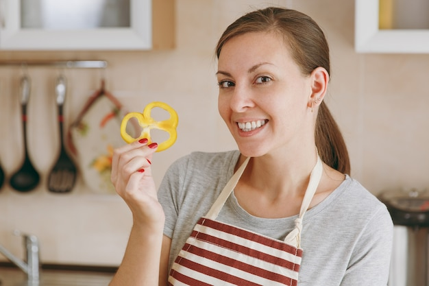 Die junge glückliche attraktive frau in einer schürze hält gelben pfeffer in der küche. diätkonzept. gesunder lebensstil. kochen zu hause. essen zubereiten.
