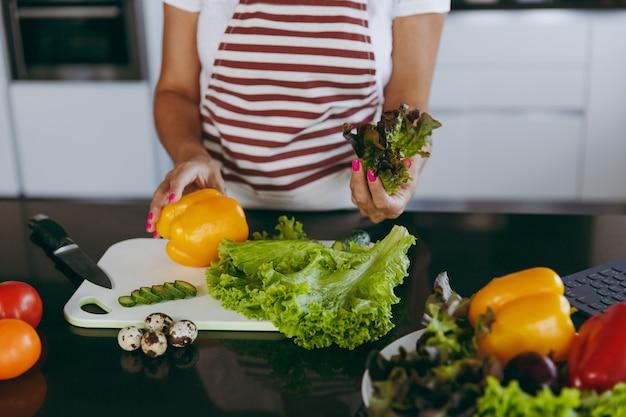 Die junge glückliche frau, die gemüse in den händen in der küche mit laptop auf dem tisch hält