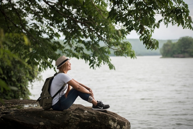 Die junge glückliche frau, die mit rucksack sitzt, genießen die natur nach wanderung.