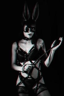Die junge herrin im ledergeschirr und in der häschenmaske hält die floggerpeitsche für bdsm-sex in ihren händen. schwarz und weiß mit glitch-effekt