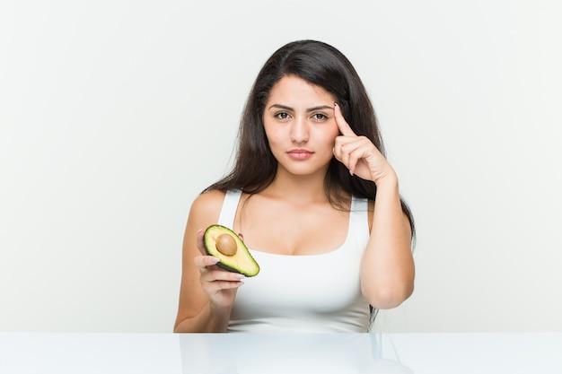 Die junge hispanische frau, die eine avocado zeigt seinen tempel mit dem finger anhält und denkt, konzentrierte sich auf eine aufgabe