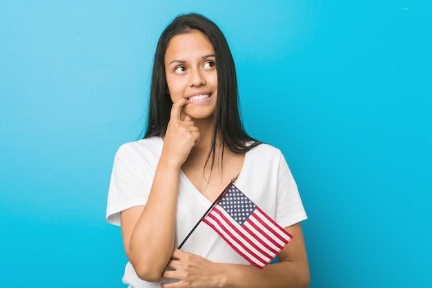 Die junge hispanische frau, die eine flagge vereinigter staaten hält, entspannte sich das denken an etwas, das einen kopienraum betrachtet.