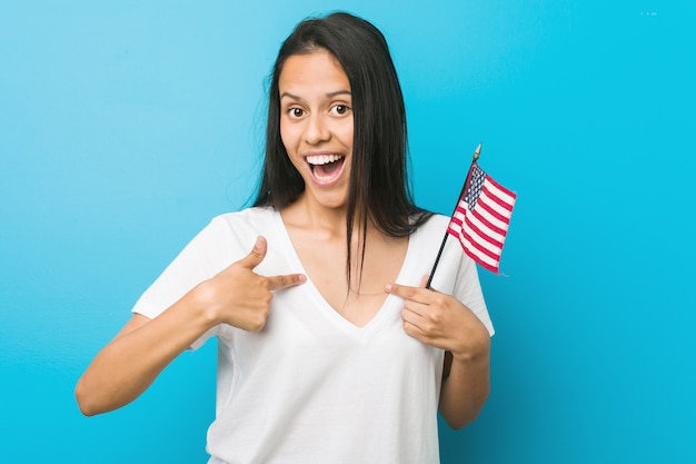 Die junge hispanische frau, die eine flagge vereinigter staaten hält, überraschte das zeigen auf und breit lächelte.