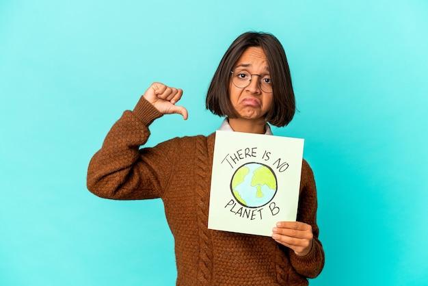 Die junge hispanische mischlingsfrau, die ein planetenplakat in der hand hält, ist stolz und selbstbewusst.