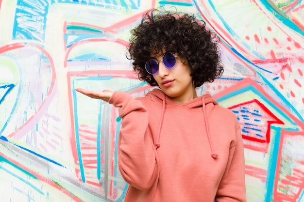 Die junge hübsche afrofrau, die glücklich sich fühlt und zufällig lächelt, schauend zu einem gegenstand oder zu einem konzept, hielt an der hand auf der seite gegen graffitiwand