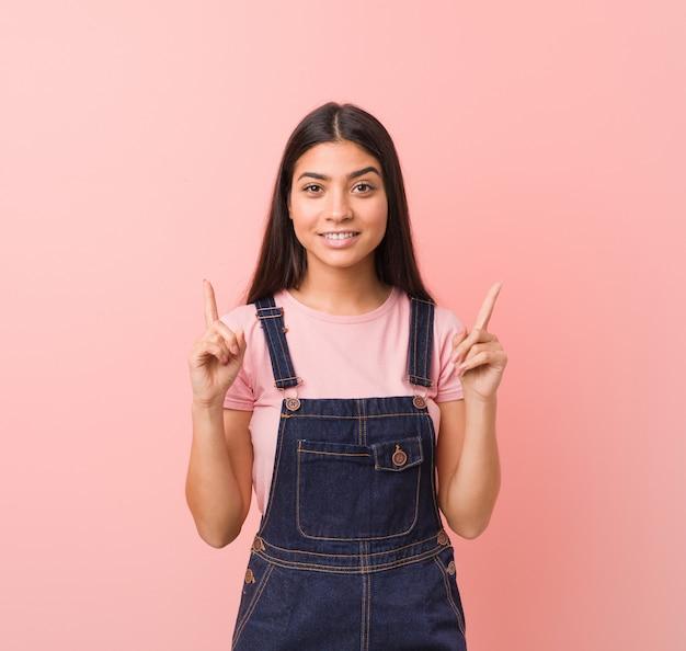 Die junge hübsche arabische frau, die einen jeanslatzhose trägt, zeigt mit beiden vorderen fingern an, die sich eine leerstelle zeigen.