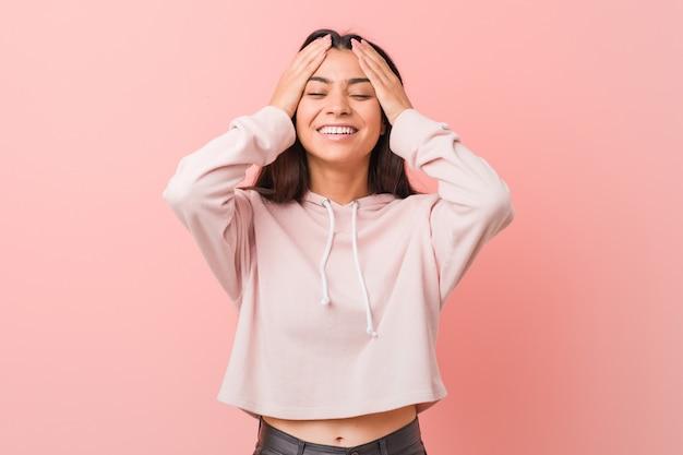 Die junge hübsche arabische frau, die einen zufälligen sportblick trägt, lacht freudig, hände auf kopf halten. glück.