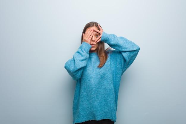 Die junge hübsche frau, die eine blaue strickjacke trägt, fühlt sich besorgt und erschrocken