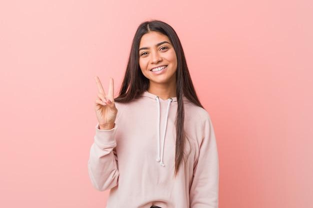 Die junge hübsche frau, die einen zufälligen sport trägt, schauen froh und sorglos und zeigen ein friedenssymbol mit den fingern