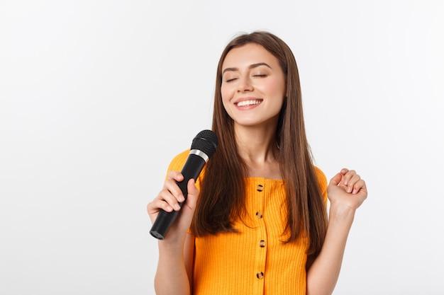 Die junge hübsche frau, die glücklich und motiviert ist, ein lied mit einem mikrofon singt, ein ereignis darstellt oder eine partei hat, genießen den moment