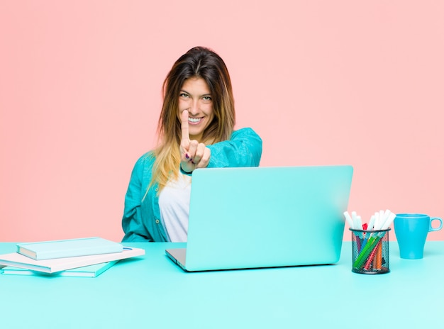 Die junge hübsche frau, die mit einem laptop lächelt stolz und sicher arbeitet, nummer eins machend, werfen sie triumphierend auf und wie ein führer glauben